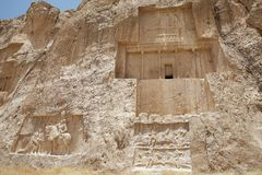 Iran. The tomb of Darius I the Great and below the relief of equestrian victory of Bahram II over enemy and athe left the relief of victory of Shapur I over the royalty free stock image