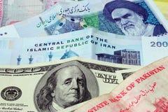 Iran and us dollar. Macro shot of iran . pakistan and united states bank notes Stock Photos