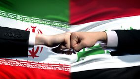 Iran vs Iraq conflict, international relations crisis, fists on flag background. Stock photo royalty free stock images