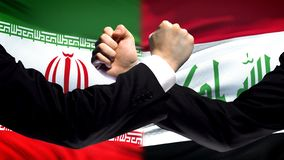 Iran vs Iraq confrontation, countries disagreement, fists on flag background. Stock photo royalty free stock photography