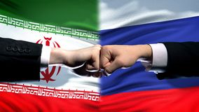 Iran vs Russia conflict, international relations, fists on flag background. Stock photo royalty free stock image
