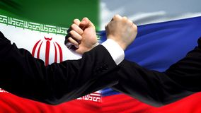 Iran vs Russia confrontation, countries disagreement, fists on flag background. Stock photo stock images