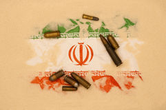 Iran at war. Iran flag covered in sand with different ammunition scatter on it Royalty Free Stock Photography