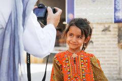 Iran, Yazd, old city - September 19, 2016: European tourist photographs a local Iranian girl in a national costume on the street. Iran, Yazd, old city Stock Photo