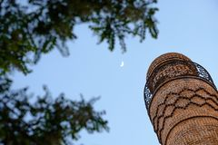 Iranian bazaar minaret with moon throughout trees in the evening o royalty free stock photo