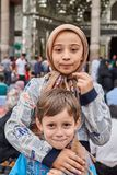 Iranian boy and girl stand near mosque, Tehran, Iran. Tehran, Iran - April 27, 2017: Iranian boy and girl in religious veil stand and hug near the Shrine of royalty free stock photo