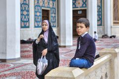 Iranian boy sitting in courtyard of mosque, Shiraz, Iran. Fars Province, Shiraz, Iran - 19 april, 2017: Shah Cheragh Shrine, Muslim woman wearing an Islamic Royalty Free Stock Images