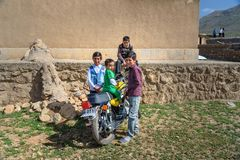Iranian boys on motobike in the village. Lorestan Province. Iran. Lorestan Province, Iran - April 1, 2018: Iranian young boys on motobike on wedding ceremony in stock images