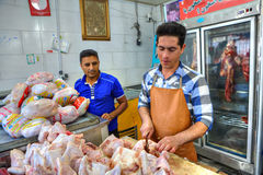 Iranian butcher cuts up chicken carcasses at butchery shop. Bandar Abbas, Hormozgan Province, Iran - 16 april, 2017: butcher cuts portions chicken meat Royalty Free Stock Image