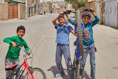 Iranian children play in a deserted street, Kashan, Iran. Kashan, Iran - April 27, 2017: Iranian male children play in a deserted street in a quarter of low Stock Images