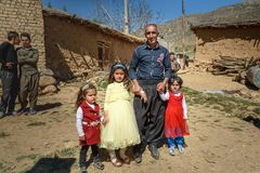Iranian family on motobike in the village. Lorestan Province. Iran. Lorestan Province, Iran - April 1, 2018: Iranian family on motobike on wedding ceremony in royalty free stock image