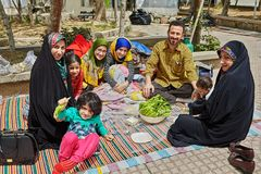 Iranian family on a picnic in the park, Tehran, Iran. Tehran, Iran - April 28, 2017: big Iranian family is spending a day off making a picnic in the park, they royalty free stock photography