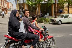 Iranian family rides a motorcycle on busy street, Kashan, Iran. Kashan, Iran - April 27, 2017: Iranian family:  man, woman in a hijab and little boy and girl Royalty Free Stock Image