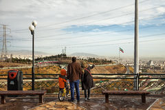 Iranian Family with Their Son on Bicycle Staring at Skyline of Tehran from a High Ground Park Royalty Free Stock Images