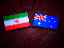 Iranian flag with Australian flag on a tree stump isolated. Iranian flag with Australian flag on a tree stump Stock Images