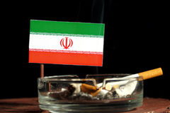Iranian flag with burning cigarette in ashtray isolated on black. Background Royalty Free Stock Images