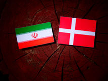Iranian flag with Danish flag on a tree stump isolated Royalty Free Stock Photos