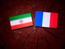 Iranian flag with French flag on a tree stump isolated. Iranian flag with French flag on a tree stump Royalty Free Stock Photography
