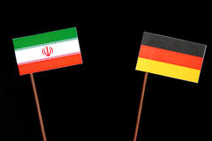 Iranian flag with German flag isolated on black. Background Royalty Free Stock Photography