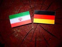 Iranian flag with German flag on a tree stump. Iranian flag with German flag on a tree stump Stock Photo