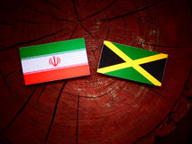 Iranian flag with Jamaican flag on a tree stump. Iranian flag with Jamaican flag on a tree stump Royalty Free Stock Image
