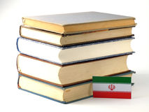 Iranian flag with pile of books isolated on white background. Iranian flag with pile of books isolated on white Royalty Free Stock Photography