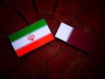 Iranian flag with Qatari flag on a tree stump isolated. Iranian flag with Qatari flag on a tree stump Royalty Free Stock Photo