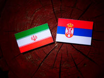 Iranian flag with Serbian flag on a tree stump isolated. Iranian flag with Serbian flag on a tree stump Royalty Free Stock Photography