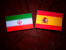 Iranian flag with Spanish flag on a tree stump. Iranian flag with Spanish flag on a tree stump Royalty Free Stock Images