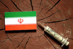 Iranian flag on a stump with syringe injecting money. In flag Stock Photos