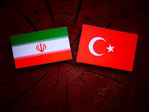 Iranian flag with Turkish flag on a tree stump. Iranian flag with Turkish flag on a tree stump Stock Photography