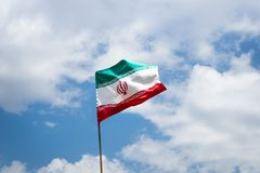 Iranian flags, flags of Islamic Republic of Iran, waving against blue sky stock photo