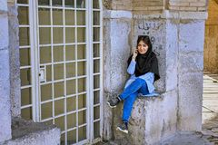 Iranian girl dressed in forced hijab, talking on phone, Isfahan. Isfahan, Iran - April 24, 2017: One young Iranian girl, wearing a forced hijab, is talking on Stock Photography