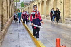 Iranian girl in school uniform going home on city street. Stock Image