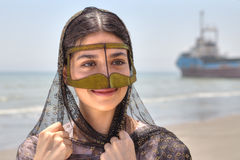 Iranian girl in traditional Muslim mask of southern Iran, smilin. Young Iranian woman in traditional mask of Muslim woman in southern Iran, smiling, standing on Stock Image