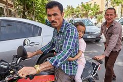 Iranian man with his daughter on a motorcycle, Kashan, Iran. Kashan, Iran - April 27, 2017: Iranian man riding with his daughter on a motorcycle, behind the Stock Images