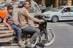 Iranian man with his son on a motorcycle, Kashan, Iran. Kashan, Iran - April 27, 2017: Iranian man with his son is riding a motorcycle on a busy street Royalty Free Stock Photos