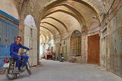 Iranian man sitting on motorcycle in vaulted lane of bazaar. Stock Photography