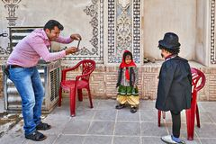Iranian man takes pictures of his children, Kashan, Iran. Kashan, Iran - April 26, 2017: Iranian man takes pictures of his children in traditional clothes in stock photography
