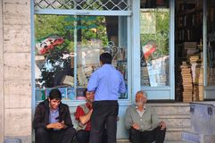 Iranian men chatting and laughing outside book store in Teheran. Iranian flag reflected in the glass of the window of a bookstore in Teheran. Men chatting and Royalty Free Stock Photography