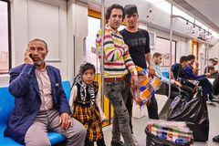 Iranian men and girl go on subway train, Tehran, Iran. Tehran, Iran - April 29, 2017: Iranian men and a girl in a hijab ride on a subway train, an elderly man Stock Image