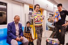 Iranian men and girl ride on subway, Tehran, Iran. Tehran, Iran - April 29, 2017: Iranian men and a little girl in a religious veil ride in a subway car stock images