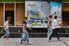 Iranian men walk down the street with shops, Tehran, Iran. Tehran, Iran - April 28, 2017: Iranian men come with bags in their hands along the street with shops Royalty Free Stock Images