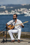 An Iranian musician playing a setar records a song adjacent to the Bosphorus in Istanbul in Turkey. Stock Images