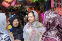 Iranian Muslim women talk in fabric store at bazaar, Shiraz. Royalty Free Stock Image