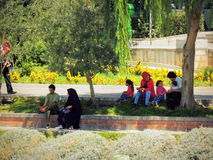 Iranian recreation at park in Isfahan. Iranian families and couples enjoy the shadows of the trees at the park and promenade along the Zayande river Royalty Free Stock Photos