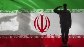 Iranian soldier silhouette saluting against national flag, military veteran. Stock footage stock footage