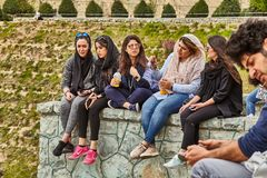 Iranian students sit in the park and chat, Tehran, Iran. Tehran, Iran - April 28, 2017: Iranian students in hijabs are sitting in the park, chatting with each Royalty Free Stock Photography