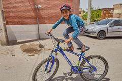 The Iranian teen shows tricks on a bicycle, Kashan, Iran. Kashan, Iran - April 27, 2017: One unknown Iranian young man shows the ability to ride a bicycle in a Royalty Free Stock Photos