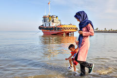 Iranian woman walks with child on Persian Gulf shore. Bandar Abbas, Hormozgan Province, Iran - 16 april, 2017: A woman in a hijab leads a little boy by the hand Royalty Free Stock Photography